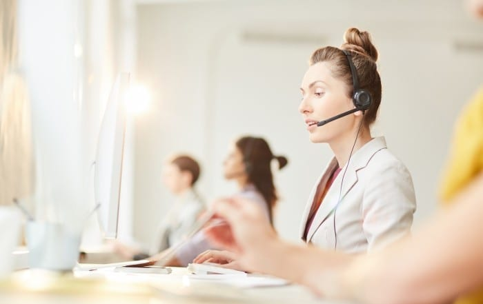Side view portrait of female hotline operator answering client calls at support line, copy space
