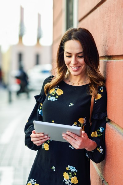 Young woman using digital tablet outdoors. Female in casual clothes with care hair in Granada, Andalusia, Spain.