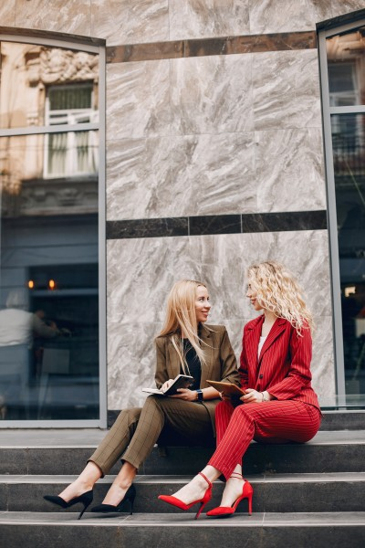 Two beautiful women working. Friends in a city. lady with a notebook