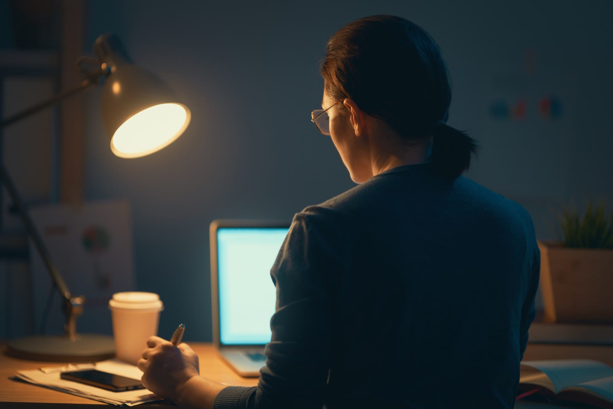 Woman working on a laptop at the night at home.