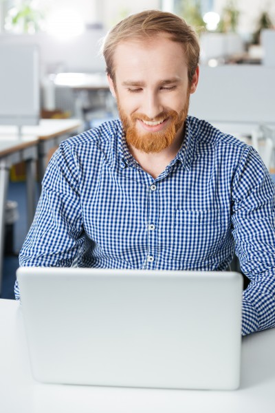 Smiling attractive young businessman using laptop working in office