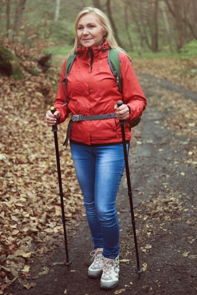 Woman with hiking poles on forest path
