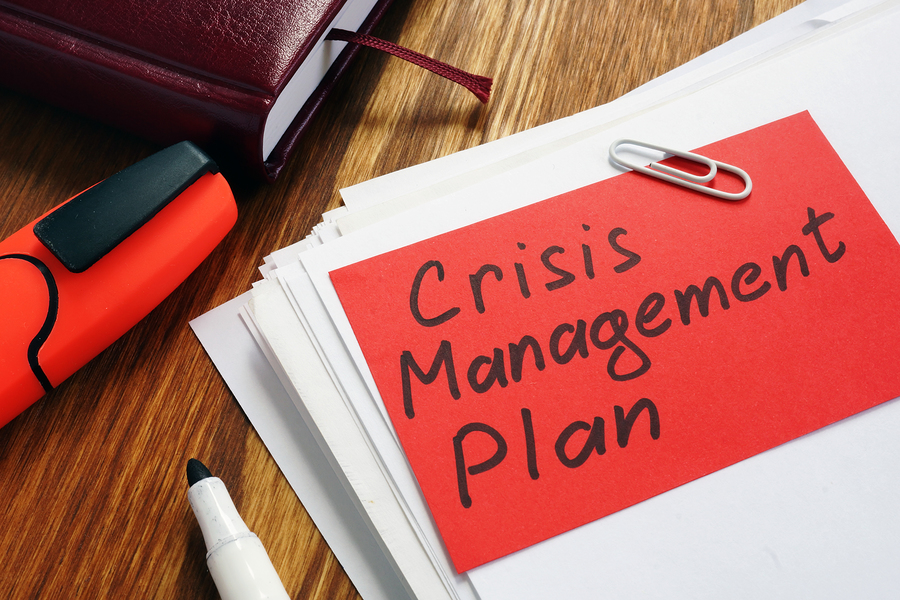 Crisis Management Plan on an office desk and papers.