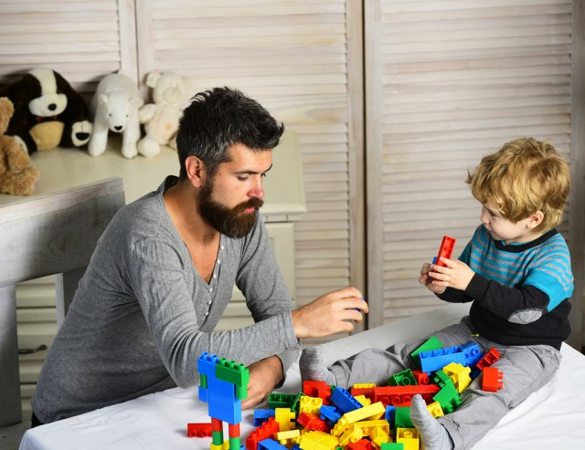 Dad and kid with toys on background build of plastic blocks. Father and son with serious faces create constructions of bricks. Family and childhood concept. Man and boy play on wooden wall background