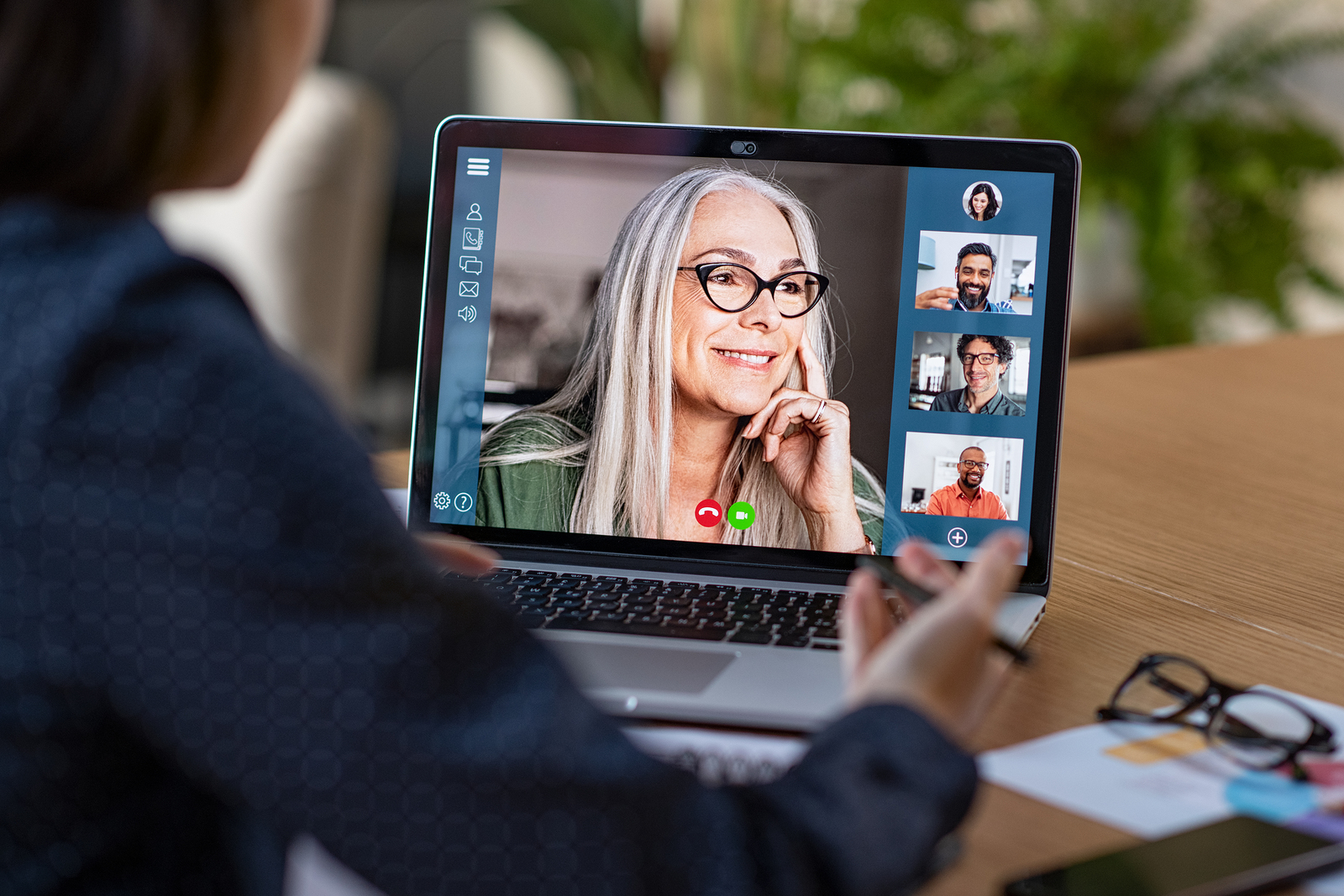 Multiethnic business team having discussion in video call. Rear view of business woman in video conference with boss and his colleagues during online meeting. Senior woman in video call with partners.