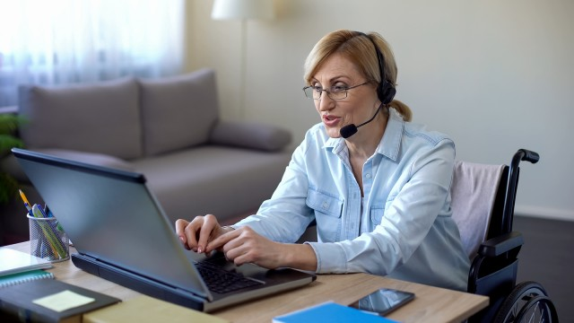 Senior disabled woman in headset applying for job from home, video conference