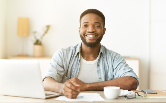 Working at home. Portrait of happy african american freelancer sitting at workplace in home office, panorama with copy space
